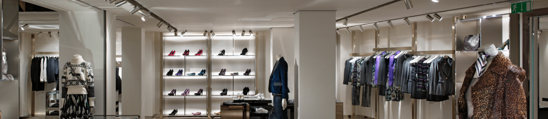image inside a clothing store with racks of clothes and shoes