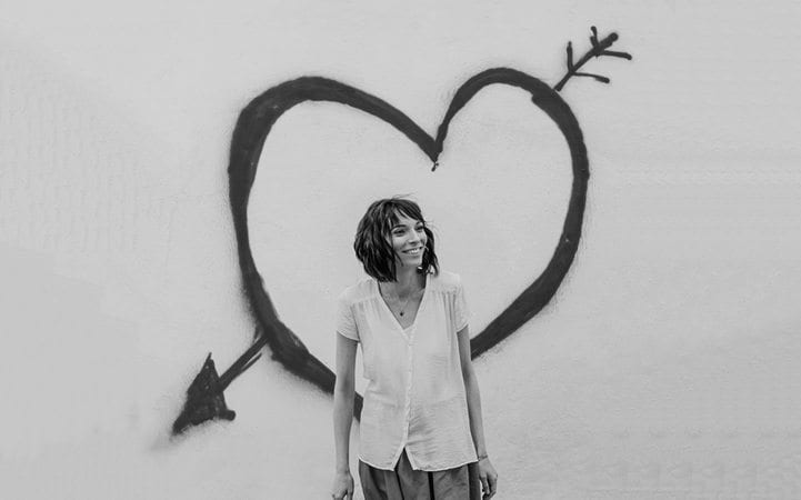 girl standing in front of heart with an arrow through it graffiti on wall