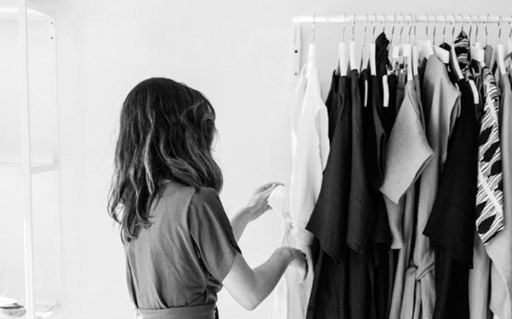 woman going through rack of clothes