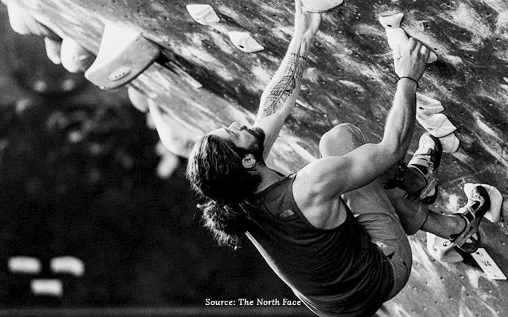 man rock climbing black and white