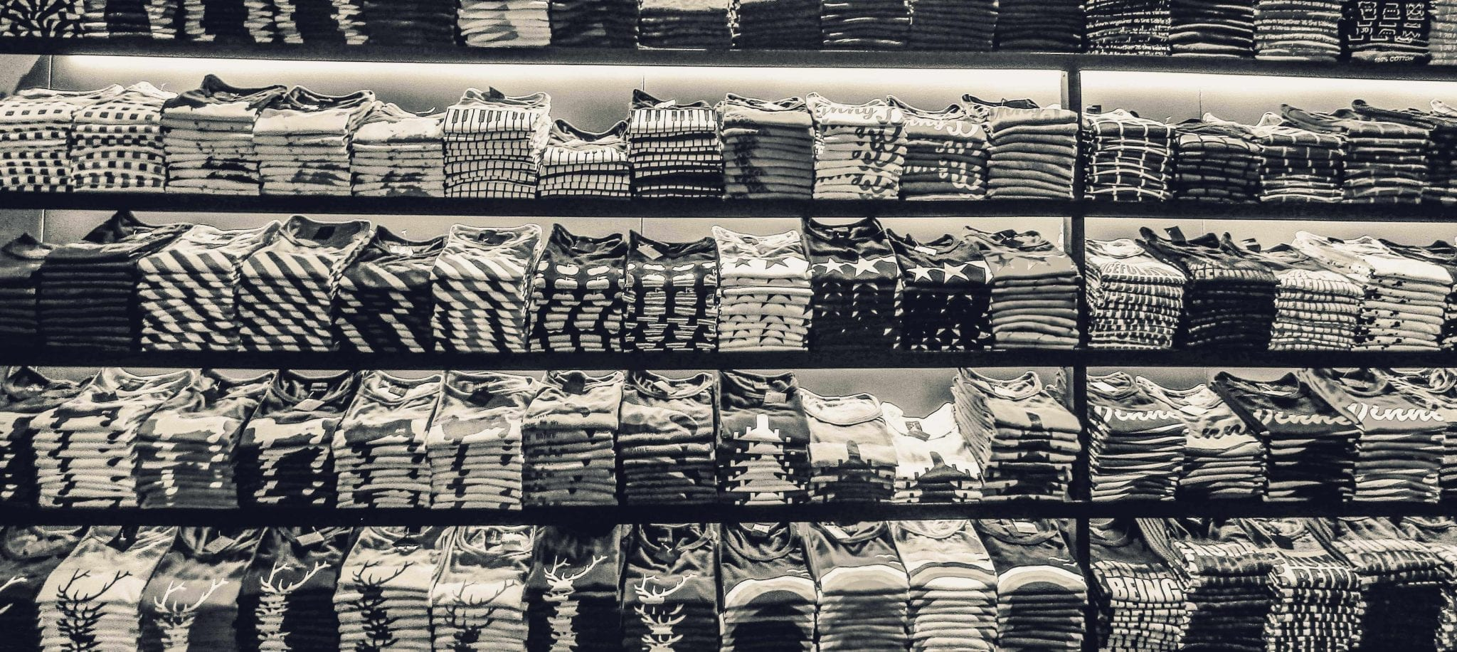 stacks of neatly folded shirts in black and white