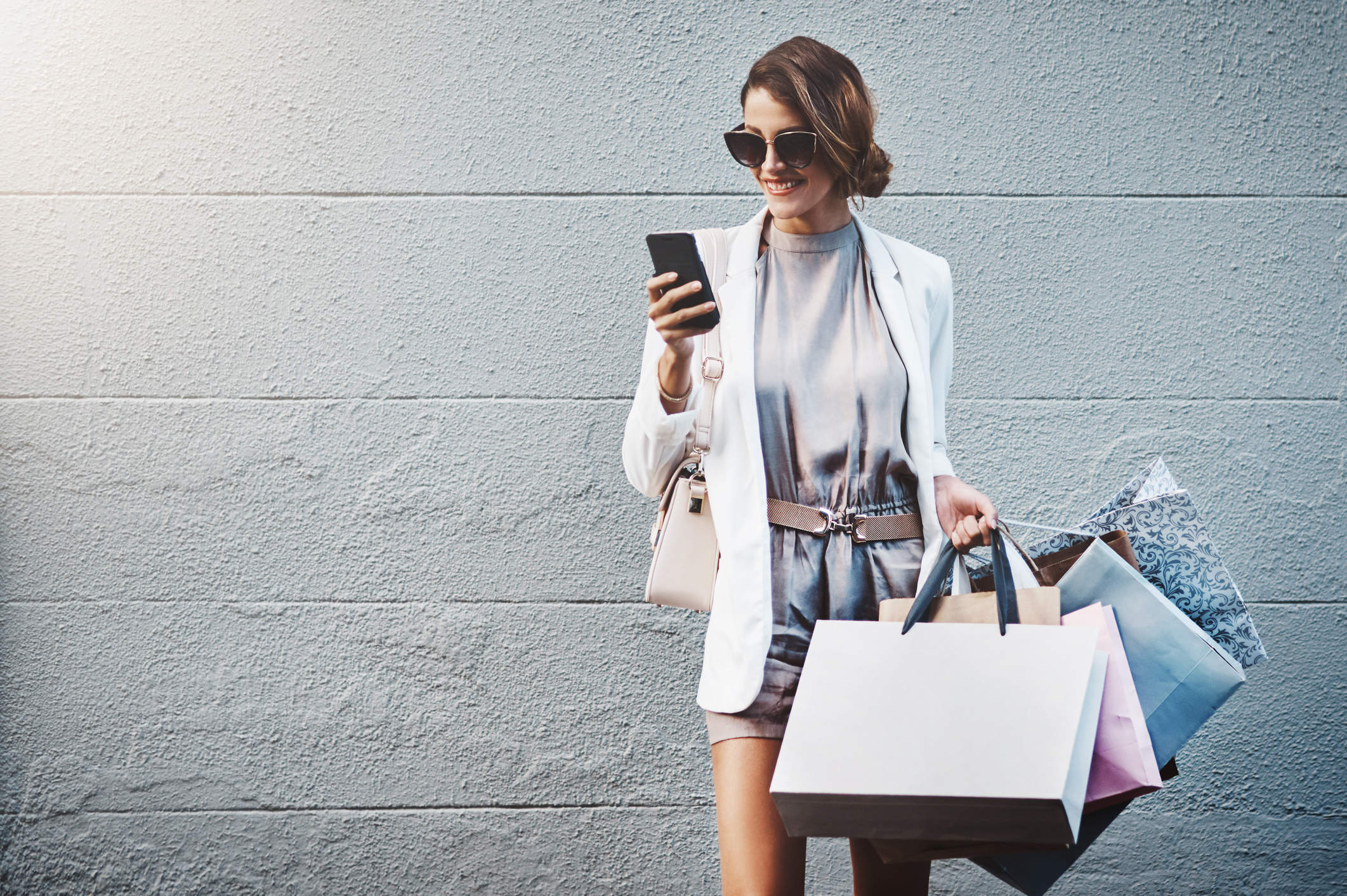 woman looking at her phone while holding shopping bags sale