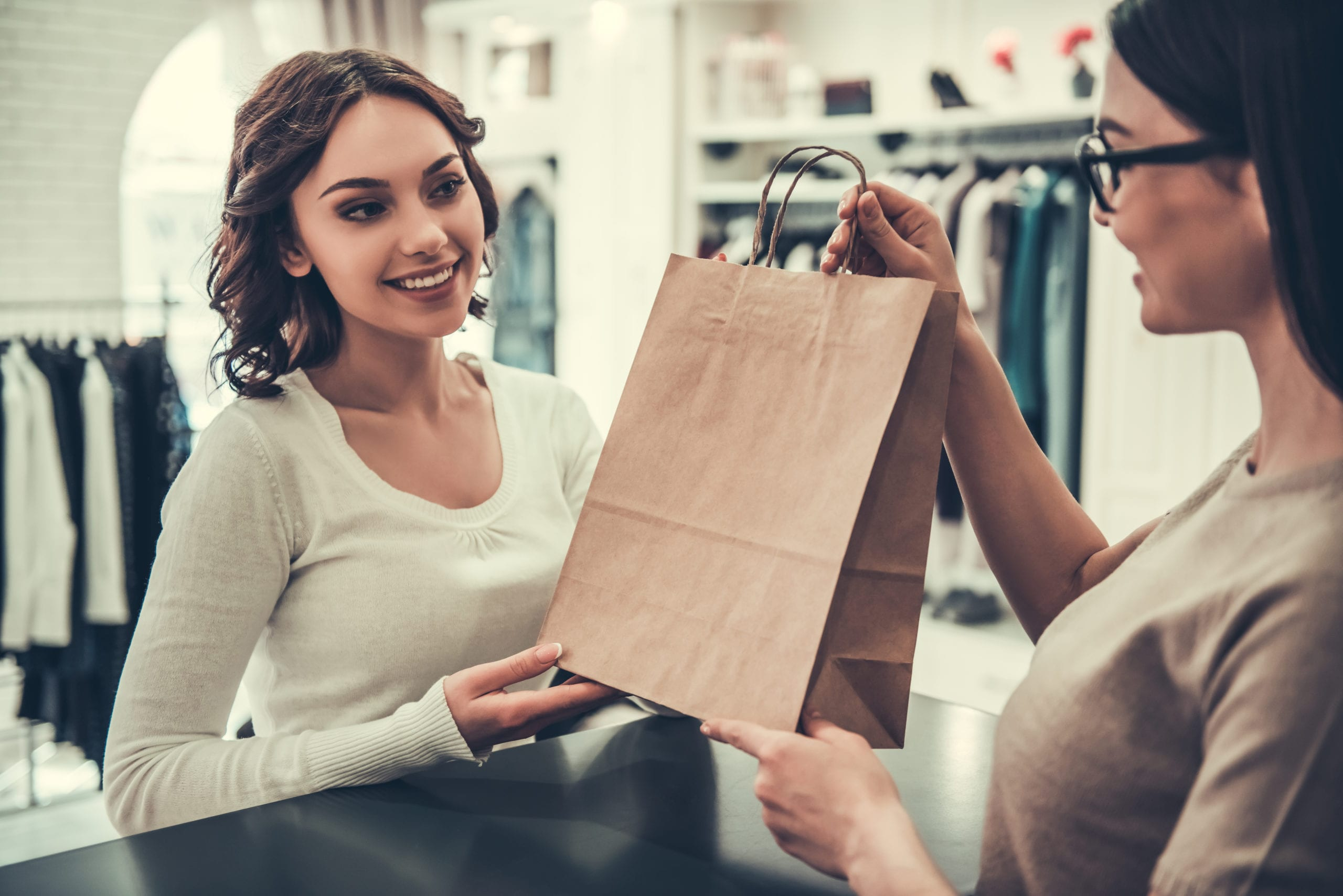 woman taking shopping bags from shop assistant