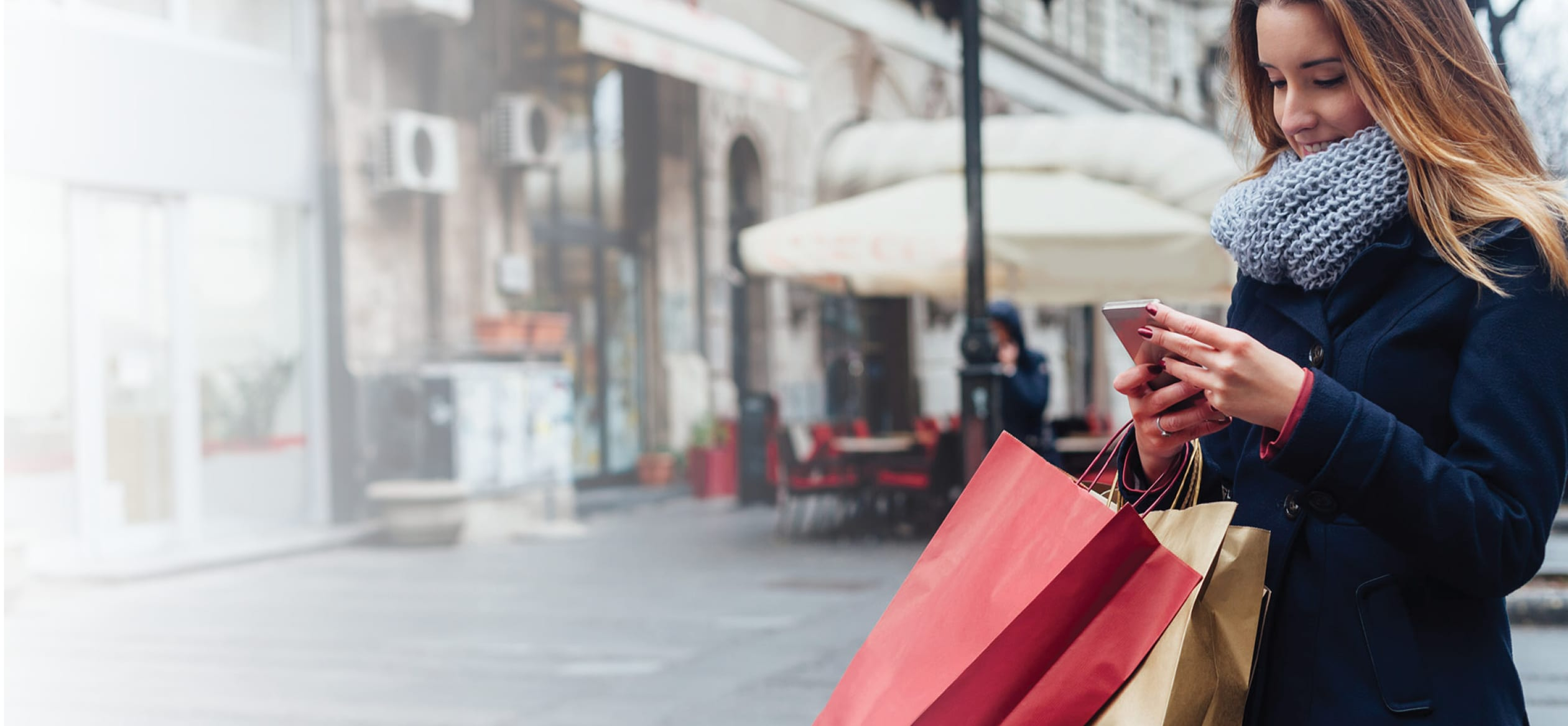 woman carrying shopping bags while on her phone