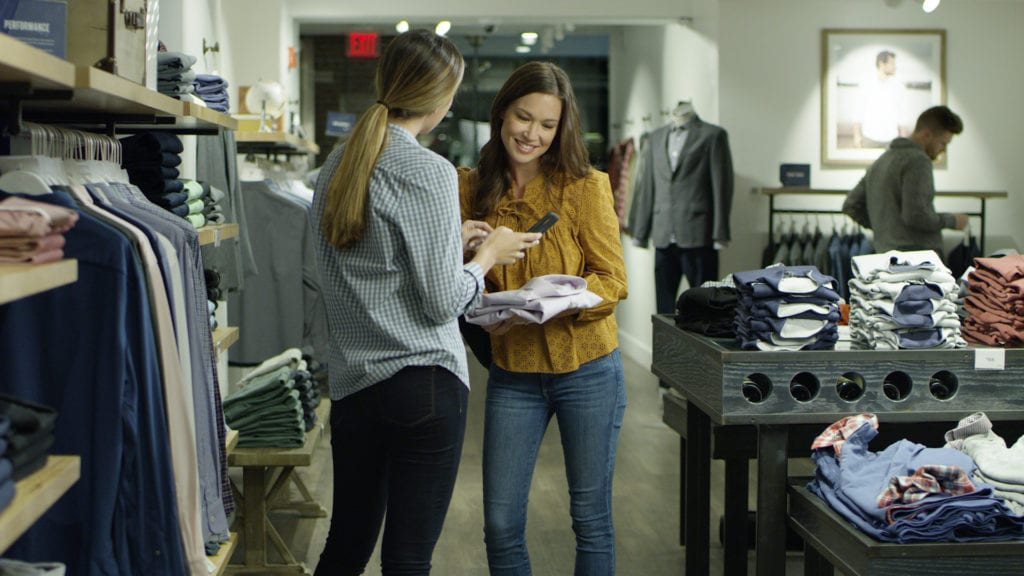 Two women in a store talking about a shirt and looking at a phone