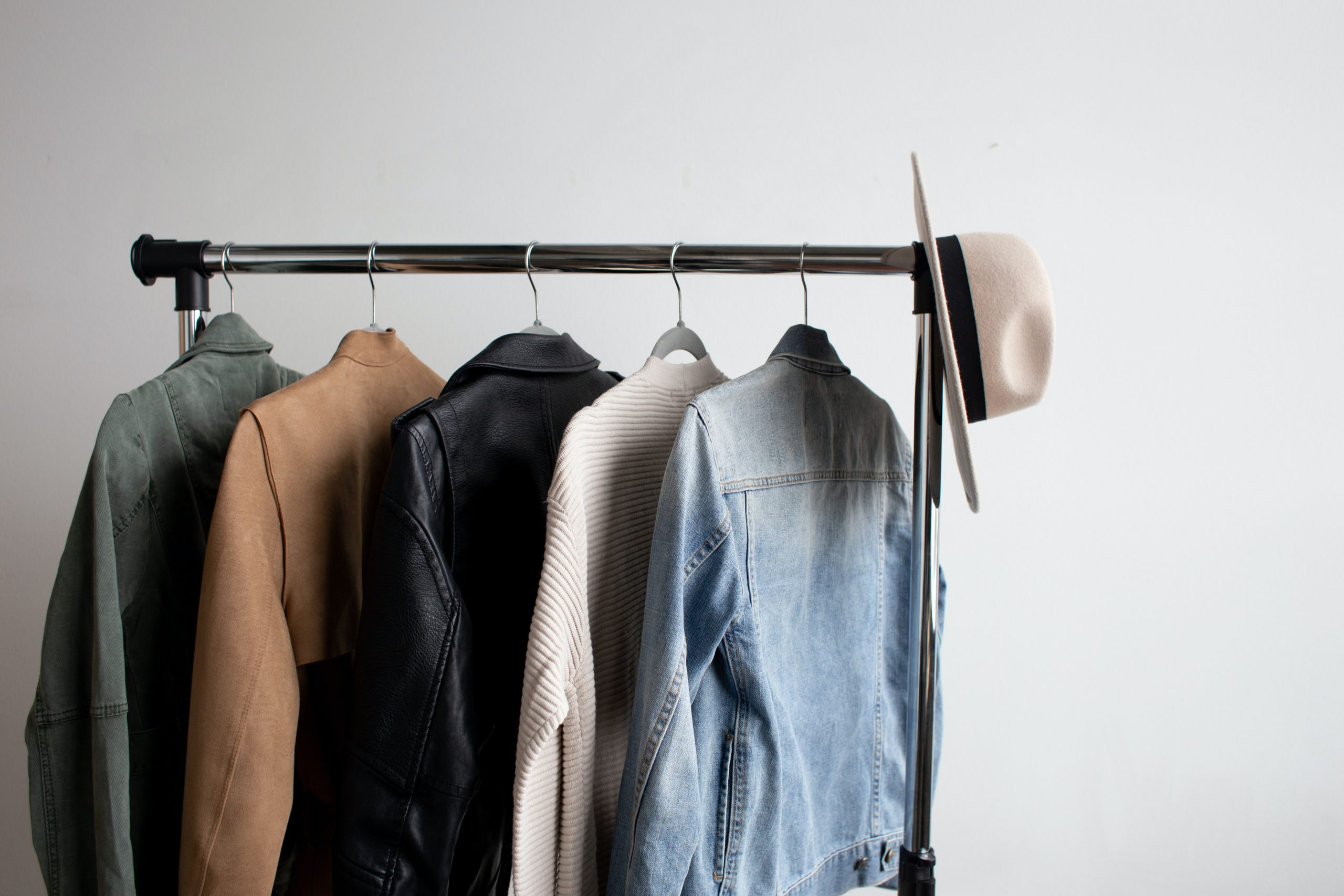 Jackets and a hat hanging on clothes rack