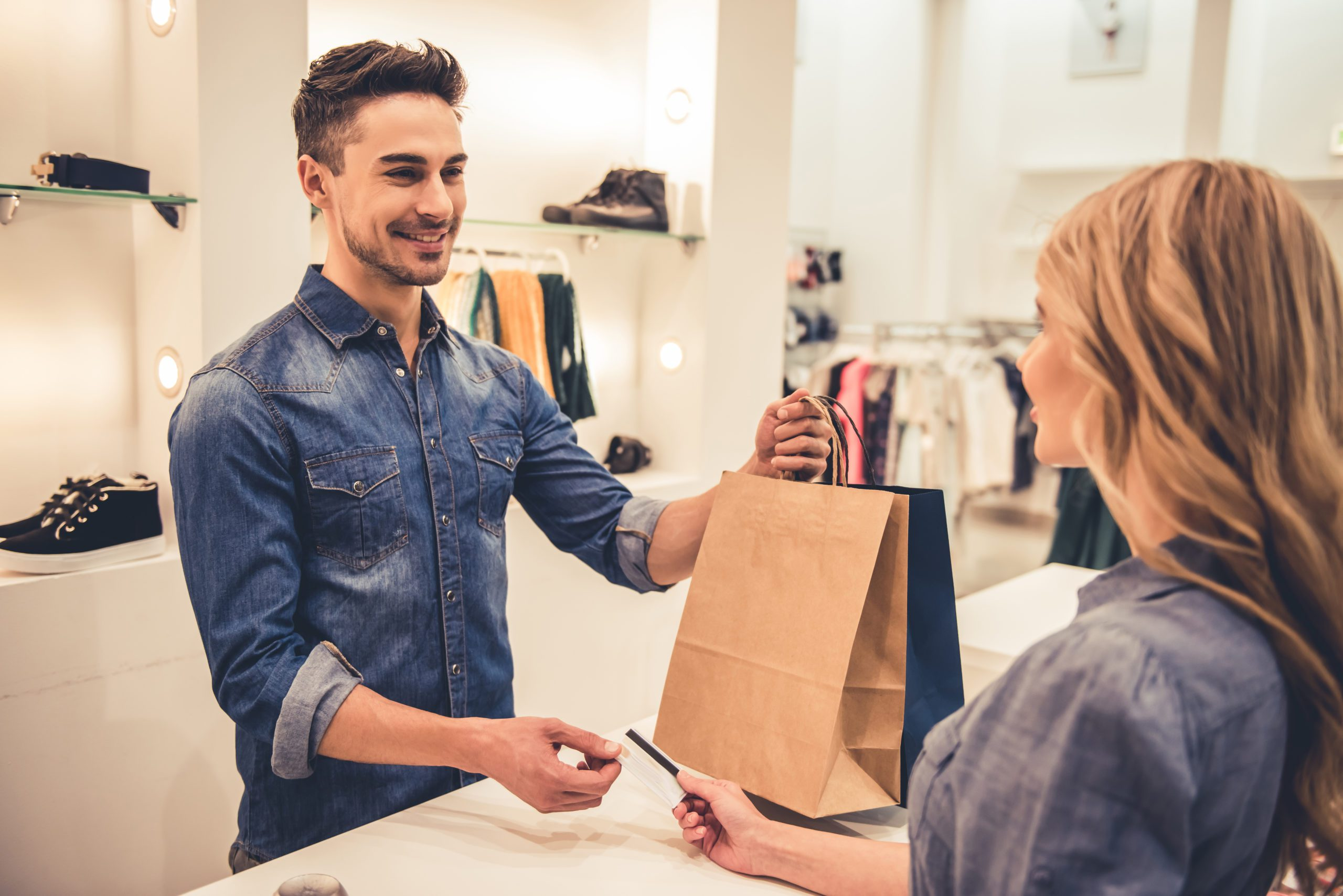 Man smiling while taking shopping bags and credit card from a female